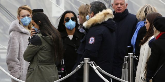 Tourists, some wearing a mask, queue to enter the Louvre museum Friday, Feb. 28, 2020 in Paris.