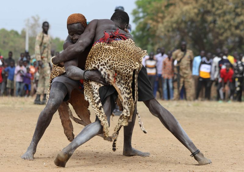 © Reuters. South Sudan's traditional wrestler from Terekeka and Yirol dress in leopard skin compete in a peace match during national championships in Juba
