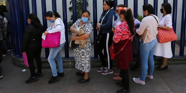 Women wear masks over their mouths as a precaution against the spread of the new coronavirus as they wait to enter as visitors the national hospital that specializes in respiratory diseases, the INER, in Mexico City, Friday, Feb. 28, 2020. Mexico's assistant health secretary announced Friday that the country now has confirmed cases of the COVID-19 virus. (AP Photo/Fernando Llano)