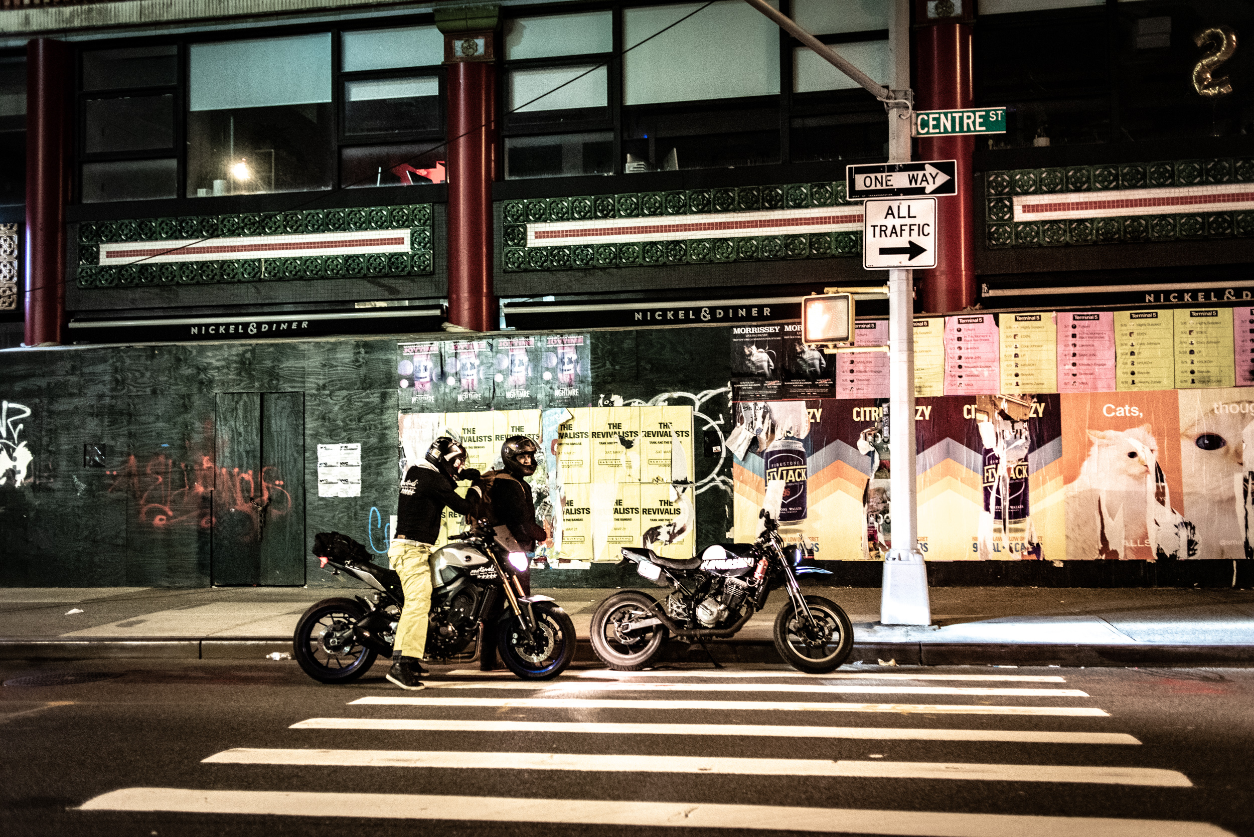 Two motorcyclists pulled over on Centre Street in Manhattan at night