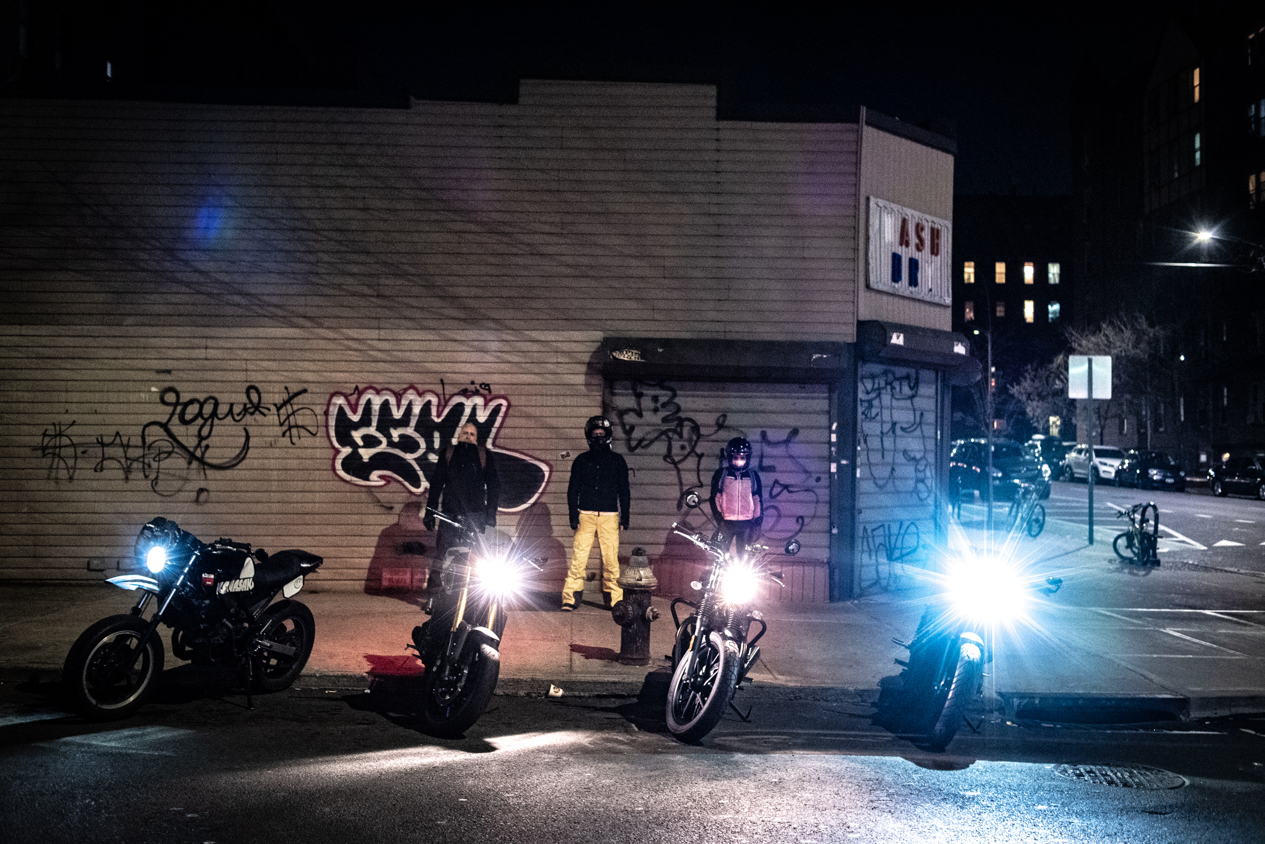 Motorcyclists lined up on a curb in Queens, New York