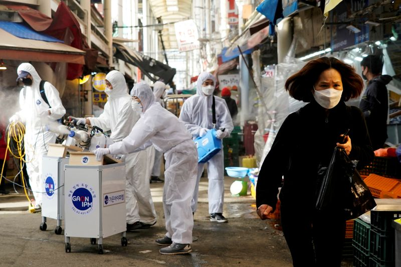 © Reuters. FILE PHOTO: A woman wearing a mask to prevent contracting the coronavirus reacts as employees from a disinfection service company sanitize a traditional market in Seoul