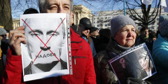 """A protester holding a poster reading """"Tired of"""" during a rally in memory of opposition leader Boris Nemtsov in St. Petersburg on Saturday."""