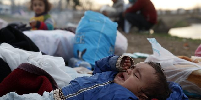 """A baby cries as migrants gather next to a river in Edirne, Turkey, near Turkish-Greek border on Wednesday, March 4, 2020. Facing a potential wave of nearly a million people fleeing fighting in northern Syria, Turkey has thrown open its borders with Greece to thousands of refugees and other migrants trying to enter Europe, and has threatened to send """"millions"""" more. (AP Photo/Darko Bandic)"""
