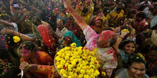An Indian man throws flowers out to devotees during Holi festival celebration at the Lord Jagannath temple in Ahmedabad, India, Tuesday, March 10, 2020.