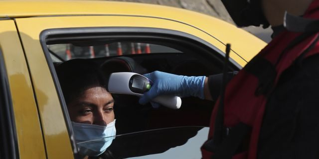 """A firefighter checks the body temperature of a commuter at a toll gate, at the northern entrance to the city of Quito, Ecuador on Tuesday. Due to the worldwide spread of the new coronavirus, the government has declared a """"health emergency,"""" restricting movement to only those who provide basic services, enacting a curfew, and closing schools. (AP Photo/Dolores Ochoa)"""