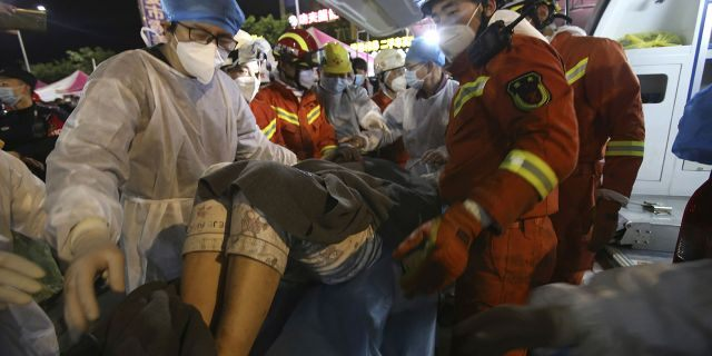 Rescuers carry a woman pulled from the rubble of a collapsed hotel to an ambulance after being trapped for 52 hours.