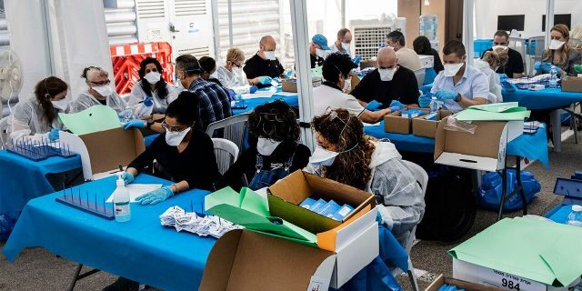 Electoral officials count ballots cast by Israelis under home quarantine after returning from Coronavirus infected zones in the city of Shoham, Israel, Wednesday. (AP Photo/Tsafrir Abayov)