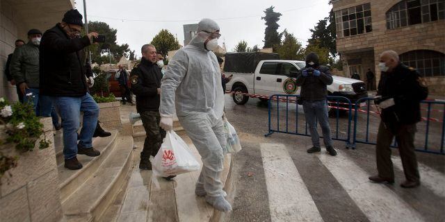 Palestinian policeman delivers supplies to the hotel staff which tested positive to coronavirus to a hotel in Bethlehem, West Bank, Friday. (AP Photo/Majdi Mohammed)