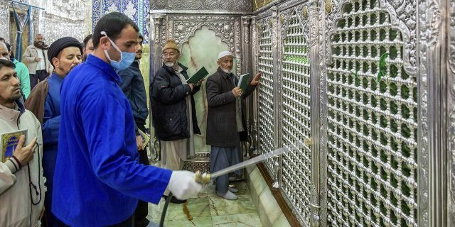 In this Monday, Feb. 24, 2020, photo, a man disinfects the shrine of Saint Masoumeh against coronavirus in the city of Qom 78 miles (125 kilometers) south of the capital Tehran, Iran. Iran's government said Monday that 12 people had died nationwide from the new coronavirus, rejecting claims of a much higher death toll of 50 by a lawmaker from the city of Qom that has been at the epicenter of the virus in the country. (Ahmad Zohrabi/ISNA via AP)