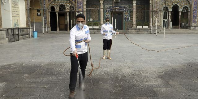 Iranian workers disinfect the shrine of the Shiite Saint Imam Abdulazim to help prevent the spread of the new coronavirus in Shahr-e-Ray, located south of Tehran, on Saturday. (AP Photo/Ebrahim Noroozi)