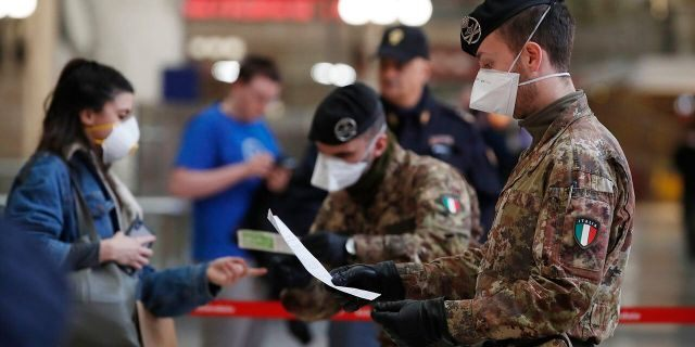 Italian police officers and soldiers check passengers leaving from Milan main train station on Monday. (AP Photo/Antonio Calanni)