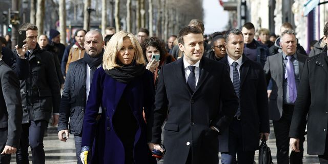 French President Emmanuel Macron and his wife Brigitte Macron on Monday walked down Paris' famous Champs-Elysees avenue in a move to send a message of confidence to the French economy amid the coronavirus crisis. (Yoan Valat, Pool via AP)