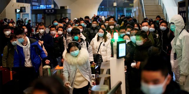 People wearing face masks arrive at a railway station in Wuhan on the first day of inbound train services resumed following the novel coronavirus disease (COVID-19) outbreak, in Wuhan of Hubei province, the epicentre of China's coronavirus outbreak, March 28, 2020.