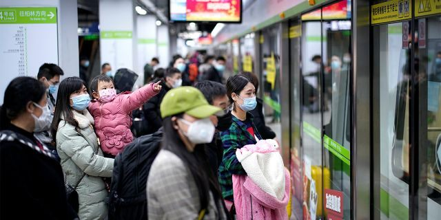 People wearing face masks wait for a subway train on the first day the city's subway services resumed following the novel coronavirus disease (COVID-19) outbreak, in Wuhan of Hubei province, the epicentre of China's coronavirus outbreak, March 28, 2020.