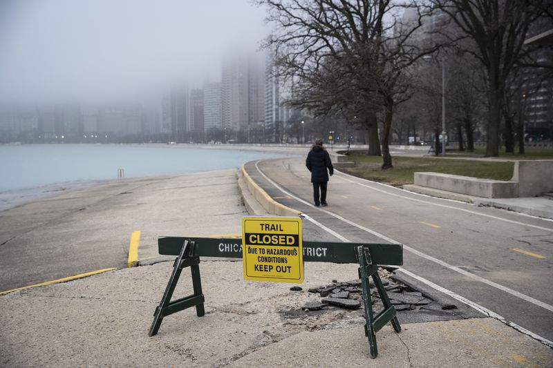 "A man ignores a ""trail closed"" sign on the Lakefront Trail near Oak Street Beach as the city closes the area to pedestrians amid fears of the coronavirus pandemic, Thursday morning, March 26, 2020."