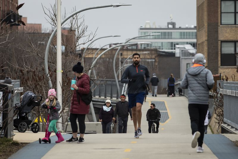 Despite a stay-at-home order from Gov. J.B. Pritzker during the coronavirus pandemic, people walk and exercise on The 606 trail near Artesian Avenue, Thursday morning, March 26, 2020.