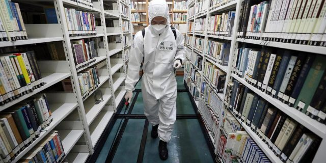 An army soldier sprays disinfectant to curb the spread of the coronavirus at a library in Daegu, South Korea, Wednesday, March 25, 2020.