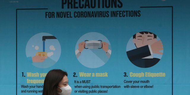 A woman wearing a face mask passes by a poster about precautions against the coronavirus in Seoul, South Korea, Thursday, March 26, 2020.