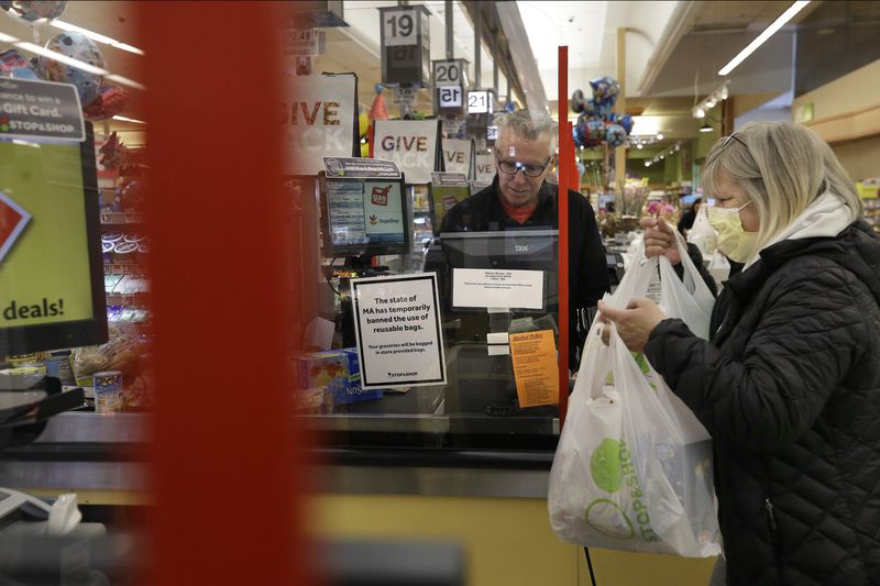 Cashier George Wallace, center, works behind a plastic shield as a shopper, right, places groceries in a cart Thursday at a grocery store in Quincy, Mass.