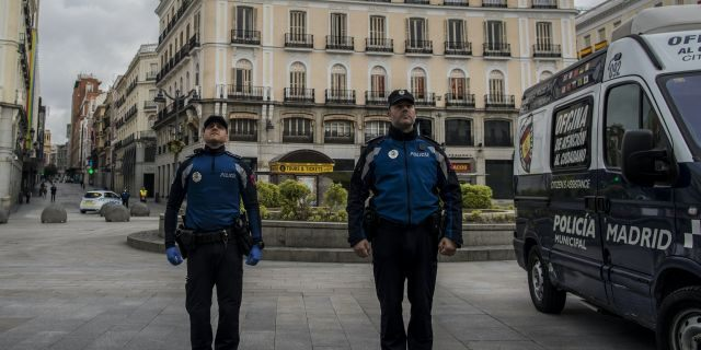 Police officers hold a minute of silence for the victims of COVID-19 as the lockdown to combat the spread of coronavirus continues in downtown Madrid, Spain, Tuesday, April 7, 2020. The new coronavirus causes mild or moderate symptoms for most people, but for some, especially older adults and people with existing health problems, it can cause more severe illness or death. (AP Photo/Manu Fernandez)
