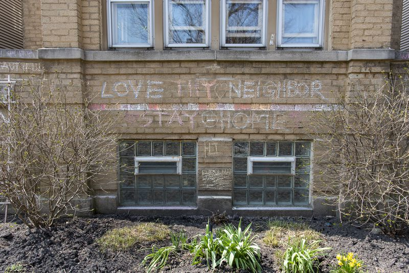 """A building with a chalk sign that asks to """"Love Thy Neighbor"""" and to """"Stay Home"""" in the Albany Park neighborhood, Tuesday."""