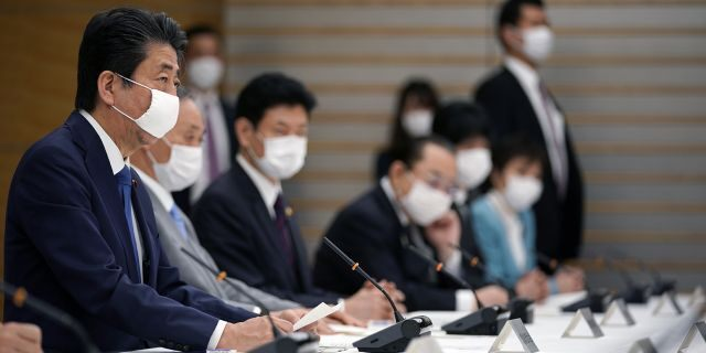 Japanese Prime Minister Shinzo Abe, left, speaks during a meeting of the headquarters for measures against the coronavirus disease at the prime minister official residence in Tokyo, Japan, Monday, April 6, 2020.