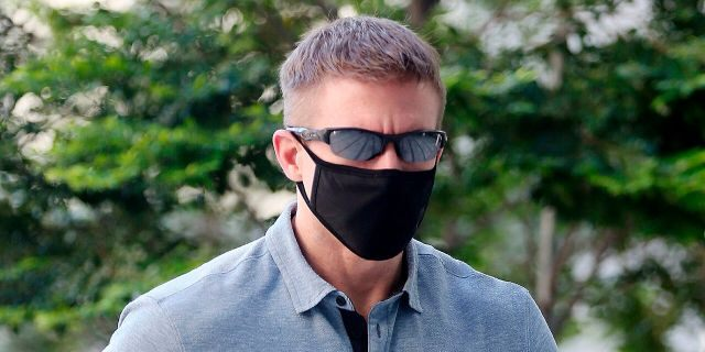 In this May 13, 2020, photo, Brian Dugan Yeargan, wearing a face mask and sunglasses, walks outside the Singapore State Court in Singapore. The 44-year-old American pilot has been jailed for four weeks for breaching a quarantine order in Singapore. Local media reported that Brian Dugan Yeargan was sentenced by a court Wednesday, May 13 for leaving his hotel room for three hours to buy masks and a thermometer. (The Straits Times via AP)