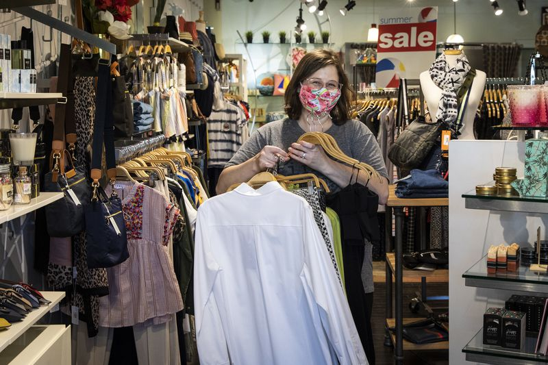 Becky Jackson, 37, of Evanston, organizes racks of clothing at the resale shop Notice, at 2112 Central St. in Evanston, which opened for the first time in weeks, Friday afternoon, May 29, 2020, as Illinois entered Phase 3 of Gov. J.B. Pritzker's reopening plan for the state.