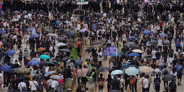 """Pro-democracy protesters march during a protest against Beijing's national security legislation in Hong Kong, May 24. Hong Kong's pro-democracy camp has sharply criticized China's move to enact national security legislation in the semi-autonomous territory. They say it goes against the """"one country, two systems"""" framework that promises the city freedoms not found on the mainland. (AP Photo/Vincent Yu)"""