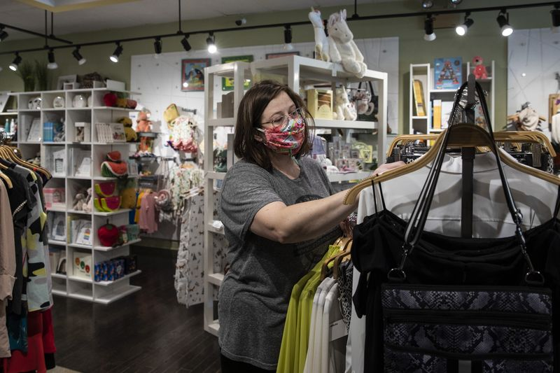 Becky Jackson, 37, of Evanston, organizes racks of clothing at the retail store Notice, 2112 Central St., Evanston, which opened Friday for the first time in weeks under the relaxed guidelines that require social distancing and set capacity limits.