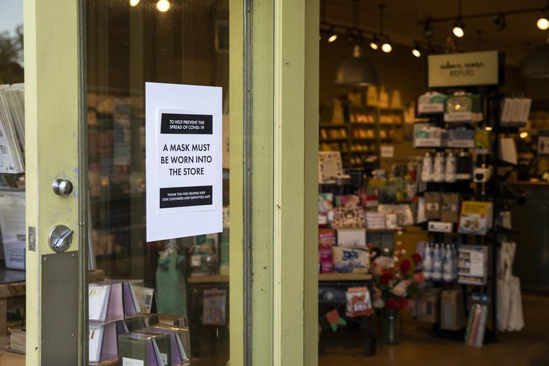 A sign indicates customers have to wear masks while shopping at the newly reopened Paper Source, 2100 Central St., Evanston.