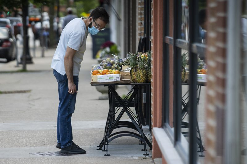 A man checks out the outdoor fruit stand that was put up at Lush Wine & Spirits Evanston, 2022 Central St.