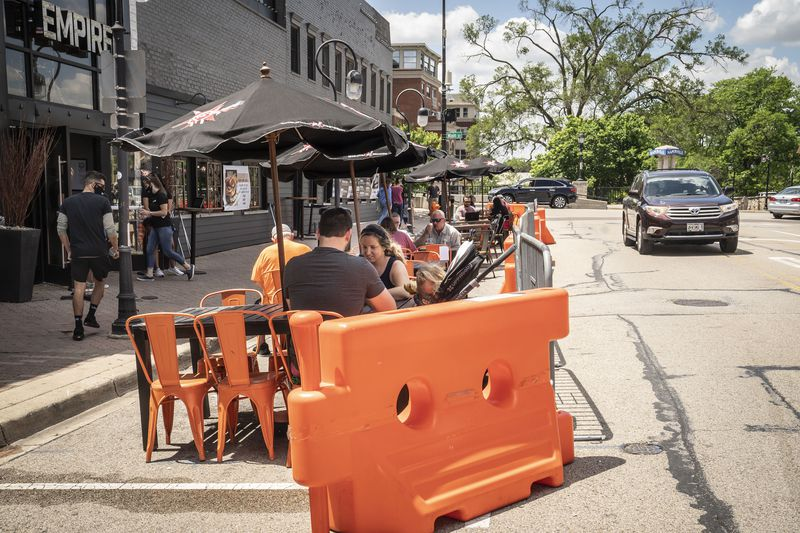 In Naperville, many restaurants expanded their sidewalk dining areas by taking and barricading a portion of the street parking area. Here, diners take advantage of the extra space outside Empire restaurant.