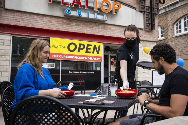 Courtney Reick, 25, serves lunch to Vasilj Stanisavljevic, 25, and his fiancé Kelly Verkoulen, 29, both from Evanston, on the patio at Flat Top Grill, 707 Church St., Evanston.