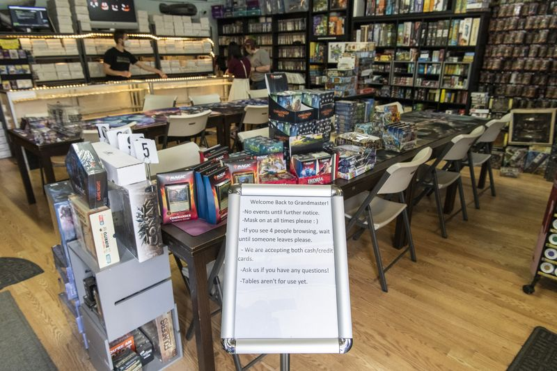 A welcome sign at the front of Grandmaster Games in Oak Park announces that the store's maximum capacity is four customers at a time and that they must wear masks at all times.