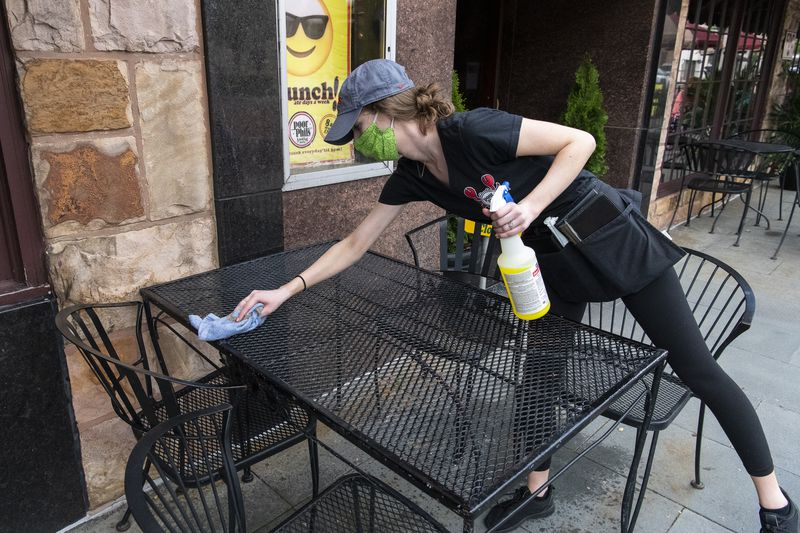 Emily Cribbin a server at Poor Phils in Oak Park, sanitizes a table for a customer on Friday.
