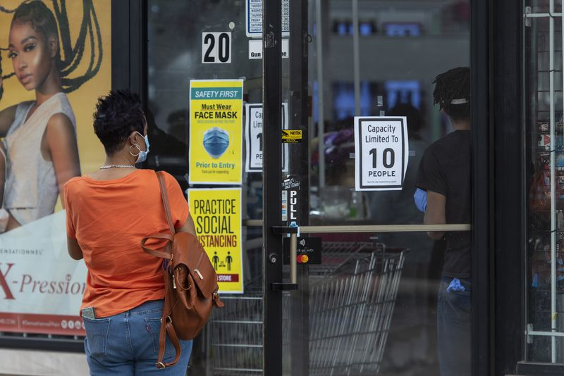 A woman waits outside of K-Stone Beauty Supply Hair and Wig store in Oak Park for a person to leave the store so she can enter.