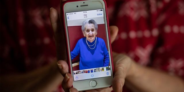In this Monday, May 18, 2020 photo, Isabel Fraile shows a picture of her mother Estefania Carretero, 93, in Madrid, Spain. Estefania Carretero was one of the residents at the Usera Center for the Elderly, who died during the coronavirus outbreak in Spain. (AP Photo/Bernat Armangue)