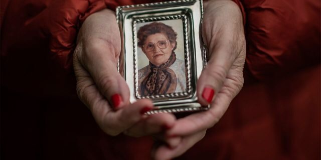 In this Thursday, May 14, 2020 photo, Teresa Navarro shows a picture of her mother Concepcion Rosinos , 97, in Madrid, Spain. Concepcion Rosinos was one of the residents at the Usera Center for the Elderly, who died during the coronavirus outbreak in Spain. (AP Photo/Bernat Armangue)