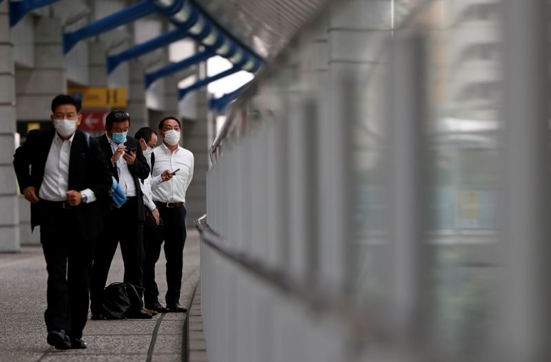 © Reuters. Businessmen wearing protective face masks are seen on a pedestrian bridge in a business district in Tokyo