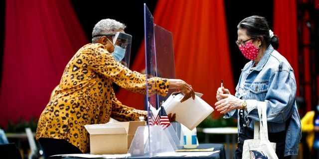 A voter, right, checks in with an election worker before casting her ballot in the Pennsylvania primary in Philadelphia, Tuesday, June 2, 2020. (AP Photo/Matt Rourke)