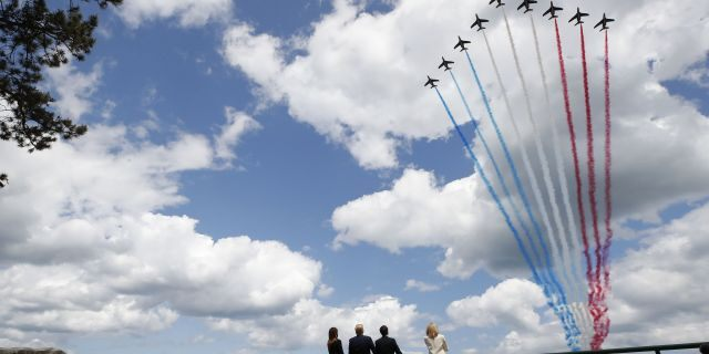 FILE - In this Thursday, June 6, 2019 file photo, President Donald Trump, first lady Melania Trump, French President Emmanuel Macron and Brigitte Macron, watch a flyover during a ceremony to commemorate the 75th anniversary of D-Day at the American Normandy cemetery, in Colleville-sur-Mer, Normandy, France. In sharp contrast to the 75th anniversary of D-Day, this year's 76th will be one of the loneliest remembrances ever, as the coronavirus pandemic is keeping nearly everyone from traveling. (AP Photo/Alex Brandon, File)