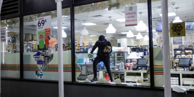 A person carries merchandise from a 7-Eleven store, Monday, June 1, 2020, in New York. (AP Photo/Frank Franklin II)