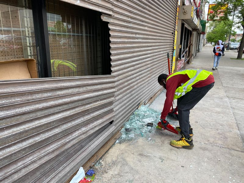 Cleaning up debris from looting on the West Side Monday.