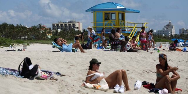 Beachgoers sunbathe as beaches are reopened with restrictions to limit the spread of the coronavirus disease (COVID-19), in Miami Beach, Florida, U.S., June 10, 2020. REUTERS/Marco Bello - RC2J6H9PQG3A