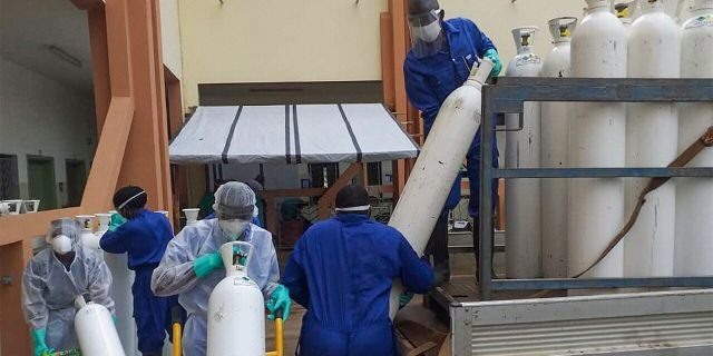Medical workers offload cylinders of oxygen at the Donka public hospital where coronavirus patients are treated in Conakry, Guinea, on Wednesday, May 20, 2020. Before the coronavirus crisis, the hospital in the capital was going through 20 oxygen cylinders a day. By May, the hospital was at 40 a day and rising, according to Dr. Billy Sivahera of the aid group Alliance for International Medical Action. Oxygen is the the facility's fastest-growing expense, and the daily deliveries of cylinders are taking their toll on budgets. (AP Photo/Youssouf Bah)