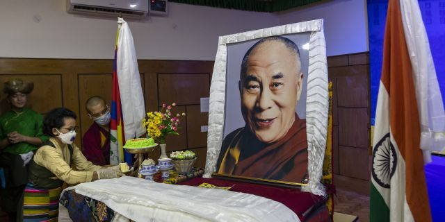 An exile Tibetan offers a piece of cake to a portrait of her spiritual leader the Dalai Lama to mark her leader's 85th birthday in Dharmsala, India, Monday, July 6, 2020. (AP Photo/Ashwini Bhatia)