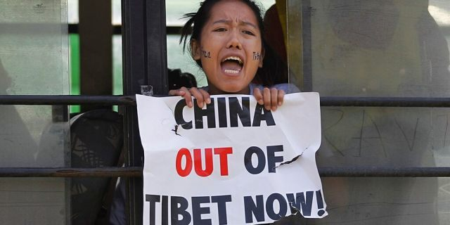 In this March 10, 2015 photo, a Tibetan exile shouts slogans against China after being detained inside a police bus during a protest in New Delhi, India. (AP Photo/Altaf Qadri, File)