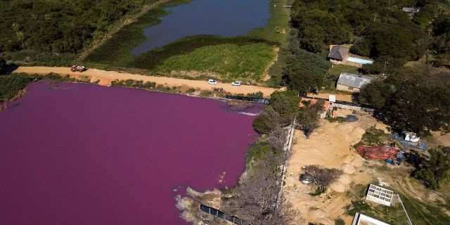 A road divides the Cerro Lagoon, where the water below the road is colored and the Waltrading S.A. tannery stands on the bank, bottom right, in Limpio, Paraguay, on Wednesday. (AP Photo/Jorge Saenz)